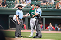 No one but team and staff on the field due to COVID-19 means no bat boys or bat girls. So, someone has to take new refreshments to the umpires. Here Brandon Howlett of the Greenville Drive (35) delivers to umpires Dylan Bradley, left, and Ervin Johnson on Sunday, May 9, 2021, at Fluor Field at the West End in Greenville, South Carolina. (Tom Priddy/Four Seam Images)