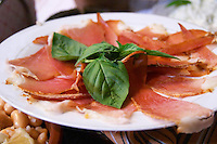 Dried dry cured ham with basil leaves on a white plate. Tradita traditional restaurant, Shkodra. Albania, Balkan, Europe.