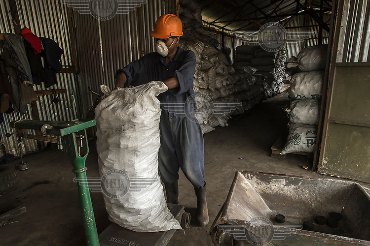 A worker collects fuel briquettes produced by Green Bio Energy based on agricultural residues and leftover coal, its combustion up to twice as slow as traditional fuels, allowing savings of 40 to 50% of the fuel budget of families.