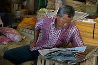 Yogyakarta, Java, Indonesia.   Man Reading Newspaper, Beringharjo Market.