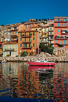 Red sailing boat anchored in Villefranche sur Mer bay surrounded with colorful houses and buildings, South of France, Mediterranean Sea, Europe