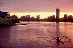 Boston, Cambridge, Massachusetts, Rower in single racing shell, sunrise over the Charles River, and the new Boston University boathouse (left)