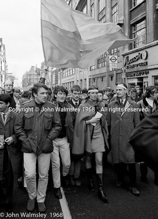 Vanessa Redgrave and other leaders, anti-Vietnam war demonstration march from Trafalgar Sq to Grosvenor Sq Sunday 17th March 1968.  I was told the headband was a Vietnamese sign of mourning for dead children.  The Vietcong flag is held aloft.  The Vietcong (National Liberation Army, NLF) was a political organisation and guerrilla army in South Vietnam which fought the Americans.