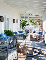 In the porch the wicker furniture is painted the same hue of blue, creating a sense of unity while contrast is provided by mixing in furniture made from varying materials and finishes. On one side of the space a pair of smooth Indonesian teak side tables play off the more textural painted wicker.