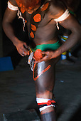Xingu Indigenous Park, Mato Grosso State, Brazil. Aldeia Afukuri (Kuikuro). Young man preparing for the festival of Taquara; body paint.