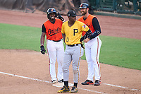 FCL Orioles Orange Donta' Williams (48) smiles on first base with coach Collin Woody (21) after getting his first professional hit during a game against the FCL Pirates Gold on August 9, 2021 at Ed Smith Stadium in Sarasota, Florida.  First baseman Norkis Marcos (13) also shown.  (Mike Janes/Four Seam Images)