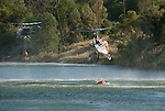 A Rogers Helicopters Bell 212 and CalFire's Bell EH-1X take water from the Mokelumne River to help suppress the Middle Bar Fire in Calaveras County on Friday.
