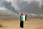 A Palestinian woman holds the national flag during clashes with Israeli security forces in tents protest where Palestinians demanding the right to return to their homeland, at the Israel-Gaza border, in Khan Younis in the southern Gaza Strip, on May 4, 2018. Photo by Ashraf Amra