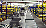 Interior large warehouse. Workers load freight on conveyor belt.