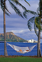Woman relaxing in hammock between palm trees while talking on a cell phone, with Diamond Head, and boat in background