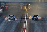 Feb. 22, 2013; Chandler, AZ, USA; NHRA funny car driver Cruz Pedregon (right) races alongside Matt Hagan during qualifying for the Arizona Nationals at Firebird International Raceway. Mandatory Credit: Mark J. Rebilas-