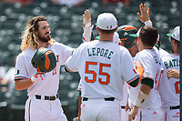 Hunter Tackett (21) of the Miami Hurricanes is greeted by his teammates as he returns to the dugout after hitting a grand slam against the Georgia Tech Yellow Jackets during Game One of the 2017 ACC Baseball Championship at Louisville Slugger Field on May 23, 2017 in Louisville, Kentucky.  The Hurricanes walked-off the Yellow Jackets 6-5 in 13 innings. (Brian Westerholt/Four Seam Images)