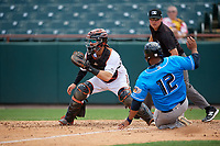Bowie Baysox catcher Brett Cumberland (28) waits for a throw as Nellie Rodriguez (12) slides home safely with umpire Mike Raines looking on during an Eastern League game against the Akron RubberDucks on May 30, 2019 at Prince George's Stadium in Bowie, Maryland.  Akron defeated Bowie 9-5.  (Mike Janes/Four Seam Images)
