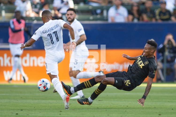CARSON, CA - MAY 8: Mark-Anthony Kaye #14 of LAFC attempts a tackle on Samuel Grandsir #11 of the Los Angeles Galaxy during a game between Los Angeles FC and Los Angeles Galaxy at Dignity Health Sports Park on May 8, 2021 in Carson, California.