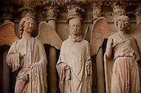 Statues at the entrance to the cathedral of Notre-Dame de Reims, Reims, France, 11 November 2015. The Smiling Angel (right) is the most famous of the cathedrals statues. She was hit by debris from a fire after being shelled by German artillery at the beginning of World War I and lost her head, which has since been restored. The statues are reddish in colour due to the molten lead that poured over them during the fire as the roof was destroyed.
