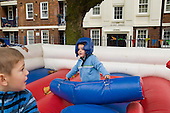 Children play Gladiators in an inflatable ring at Fisherton Estate street party, London