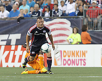 New England Revolution forward Chad Barrett (9) works to clear ball as Houston Dynamo midfielder Boniek Garcia (27) disrupts. In a Major League Soccer (MLS) match, Houston Dynamo (orange) defeated the New England Revolution (blue), 2-1, at Gillette Stadium on July 13, 2013.