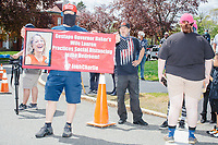 """People gather for an anti-lockdown protest organized by the alt-right group Super Happy Fun America near the home of Massachusetts governor Charlie Baker in Swampscott, Massachusetts, on Sat., May 16, 2020. The protest was in defiance of Massachusetts orders mandating face coverings and social distancing and prohibiting gatherings larger than 10 people during the ongoing Coronavirus (COVID-19) global pandemic. The state's stay-at-home order is expected to be updated on May 18, 2020, with a phased reopening plan issued by the governor as COVID-19 cases continue to decrease. Anti-lockdown protests such as this have become a conservative cause and have been celebrated by US president Donald Trump. Many of the protestors displayed pro-Trump messages or wore Trump campaign hats and shirts with phrases including """"Trump 2020"""" and """"Keep America Great.""""<br /> <br /> The signs here read """"Gestapo Governor Baker's Wife Lauren Practices Social Distancing in the Bedroom!"""" Super Happy Fun America, organizers of the protest, are an alt-right organization best known for creating the 2019 Boston Straight Pride Parade."""