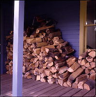 Stacked firewood against side of house<br />