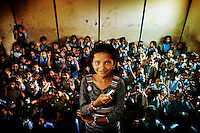 "Dewi stands in front of her class holding a piece of chalk. .Dewi is 12 years old and lives with her parents and sister in one of the slums in Delhi. She's very chatty and very disciplined. She has a lot of friends with whom she likes to play hide and seek. ""When I grow up, I want to be a teacher. Then I can teach children to read, write and count. This is very important for them since otherwise they won't get a job. I'll be a strict teacher and the kids will have to listen to me!"".."