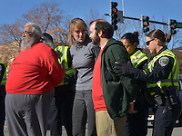 STAFF PHOTO BEN GOFF  @NWABenGoff -- 11/25/14 Fayetteville police officers arrest demonstrators David Garcia, from left, Jane Stitt and Nik (CQ) Robbins after they knelt in the roadway to block traffic during a protest organized by the OMNI Center for Peace, Justice & Ecology in front of the Washington County Courthouse in Fayetteville on Tuesday Nov. 25, 2014. Four demonstrators volunteered to make a statement by being arrested. The demonstration was in response to the decision Monday night by the St. Louis County grand jury not to indict police officer Darren Wilson, who fatally shot Michael Brown in Ferguson, Mo.