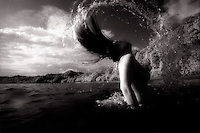 Woman in ocean coming to surface and flipping hair back<br />