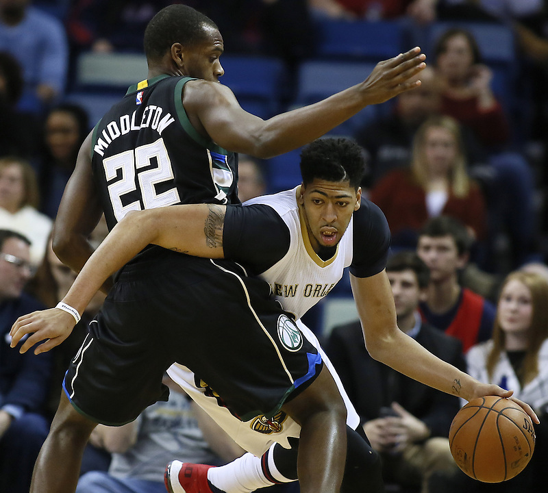 New Orleans Pelicans forward Anthony Davis, right, drives against Milwaukee Bucks guard Khris Middleton, left, during the first half of an NBA basketball game Saturday, Jan. 23, 2016, in New Orleans. (AP Photo/Jonathan Bachman)