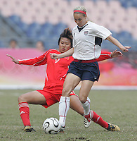 January 30, 2007: USWNT defender (2) Heather Mitts steps away from the tackle of Chinese forward (9) Han Duan during the Four Nations Tournament final at Guangdong Olympic Stadium in Guangzhou, China.  The U.S. defeated China, 2-0.