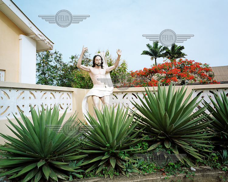 A statue of Jesus Christ with stigmata next to a house in Elmina.