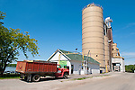Grain elevator along the shore of the Mississippi River as trucks bring their harvest of winter wheat to market