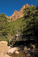 Corsica. Balagna. Hiker on suspension bridge near Bonifatu, Cirque de Bonifatu.  France..
