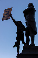 """Azaria Rivera, 23, holds a sign reading """"Trump/Pence Out Now"""" as he stands atop the statue of Samuel Adams outside Faneuil Hall at the end of the 2020 Women's March protest in opposition to the re-election of US president Donald Trump in Boston, Massachusetts, on Sat., Oct. 17, 2020."""