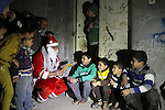A Palestinian man in Santa Claus costume distributes gifts to children as part of Christmas and New Year festivities, in Shijaiyah neighborhood, east Gaza on December 31, 2014. Photo by Mohammed Asad