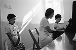 The Peoples Republic of China. Shanghai. At the Shanghai Arts Kindergarten a student waits his turn for a piano lesson. It seems that in China, as in the rest of the world, piano lessons are more popular with parents than with children.