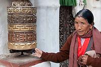 Bodhnath, Nepal.  Nepali Woman, Prayer Beads in Hand, Spinning Prayer Wheel.