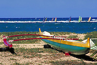 traditional outrigger canoe on Kanaha Beach. Wind surfers riding the waves in the background.  Sand, color, sports, recreation, surf sailing, sail, sailboard, boat. Hawaii USA Maui.