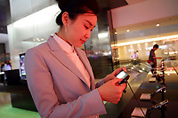 SOUTH KOREA. A member of staff looks at a cellphone inside the main showroom of Samsung, at their head-office in downtown Seoul. 2010