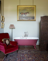 A pink-painted free-standing bath tub is dwarfed by the velvet-upholstered armchair and regal cushion