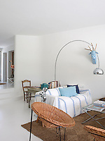 The whitewashed living room walls have been left bare apart from a contemporary blue and white reindeer head sculpture