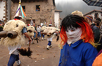 ZUBIETA, NAVARRE- JANUARY 31: A disguised  child near a group of 'Zanpantzar', people dressed in sheep fur and big cowbells tied to their back, march across Zubieta village during an ancient traditional carnival on January 31, 2006. Zanpantzar´s march trough Zubieta farmhouses and streets sounding their cowbells to wake up the earth for a good new farmer year and keep far away all bad spirits . Photo by Ander Gillenea