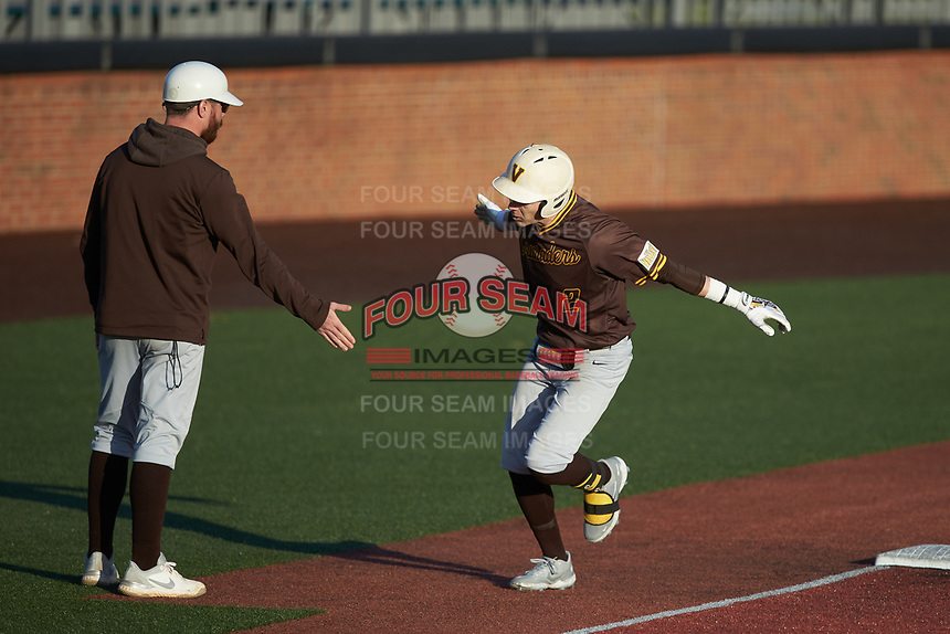 Damon Jorgensen (2) of the Valparaiso Crusaders slaps hands with third base coach Casey Fletcher after hitting a home run during the game against the Western Kentucky Hilltoppers at Nick Denes Field on March 19, 2021 in Bowling Green, Kentucky. (Brian Westerholt/Four Seam Images)