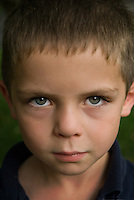 Young boy looks up at camera.
