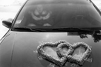 Ukraine. Province of Kiev. Slavutich. A woman, seated in a car, waits for a couple who just got married at the town hall. Two hearts made of paper are taped on the coach's hood. Heart-shaped floral arrangement. The town of Slavutich was created after the catastrophe which took place on april 1986 at 1.23 am with the explosion of reactor No 4 at Chernobyl atomic power station. Slavutich is distant 60 km from the power station and was newly built after the evacuation of the inhabitants from both towns of Pripyat and Chernobyl. © 2006 Didier Ruef