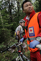 A rider stands in the forest after crashing into a tree head first. He had a lucky escape, was checked by medics  and was able to continue after a few minutes. Grenserittet is a 80km mountain bike race starting in the Swedish town of Strömstad, ending up in the Norwegian town Halden. The interest for these kind of bike races has exploded in Norway the last few years, particularly with middle age affluent men.