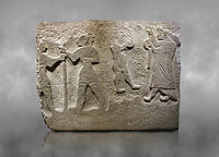Alaca Hoyuk Hittite monumental relief sculpted orthostat stone panel. Andesite, Alaca, Corum, 1399 - 1301 B.C. Anatolian Civilizations Museum, Ankara, Turkey<br /> <br /> The rightmost figure wears a long coat and tailed dress. With both hands, he holds a sceptre with a ring in the middle. This item is thought to be a cult object in Assyria reliefs. The pointed and twisted tips of his shoes also show that he is in a high rank.  <br /> <br /> Against a grey art background.