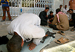 A Shiite cleric Moqtada al-Sadr's Mehdi militia militant prays while his comrades have lunch near Imam Ali Shrine in Najaf on May 15, 2004.  (photo by Khampha Bouaphanh)