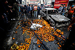 Fruit is scattered accross the street near a charred car after a fire that broke out in a market in the refugee camp of Nuseirat in central Gaza Strip, on March 5, 2020. Photo by Osama Baba
