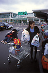 Mother and baby Asda supermarket doing weekly shopping loading up the car with baby asleep in baby chair fixed to trolley London 1990s UK