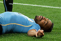 Alvaro Pereira of Uruguay lays unconscious after a challenge from Raheem Sterling of England