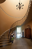 A sweeping, cantilevered staircase with delicate wrought-iron banisters curves up from the entrance hall